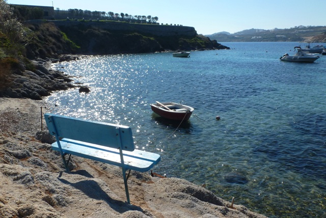 Seat overlooking Ornos Beach on Mykonos, Greece - by Zoe Dawes
