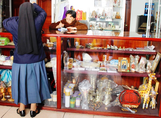 Nun stocking up on religious supplies in Convent Shop, Quito Ecuador - image Zoe Dawes